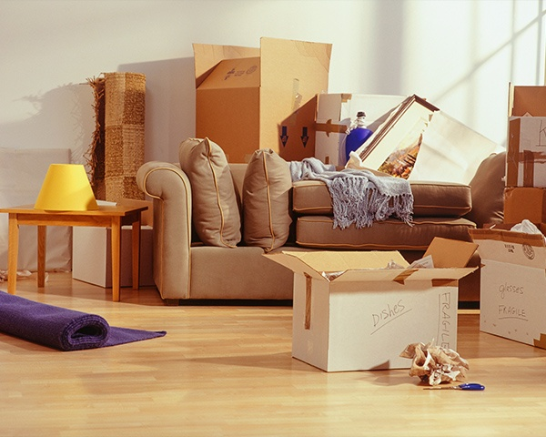 Moving boxes and items packed in a kitchen with couch and side table.