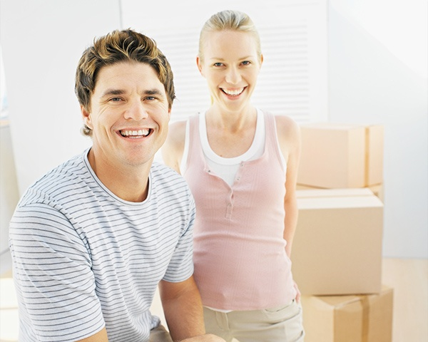 Wisconsin husband and wife smiling with moving boxes in background.